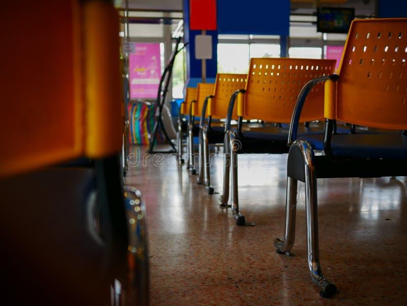 Cadeiras amarelas vazias na estação de ônibus foto de stock