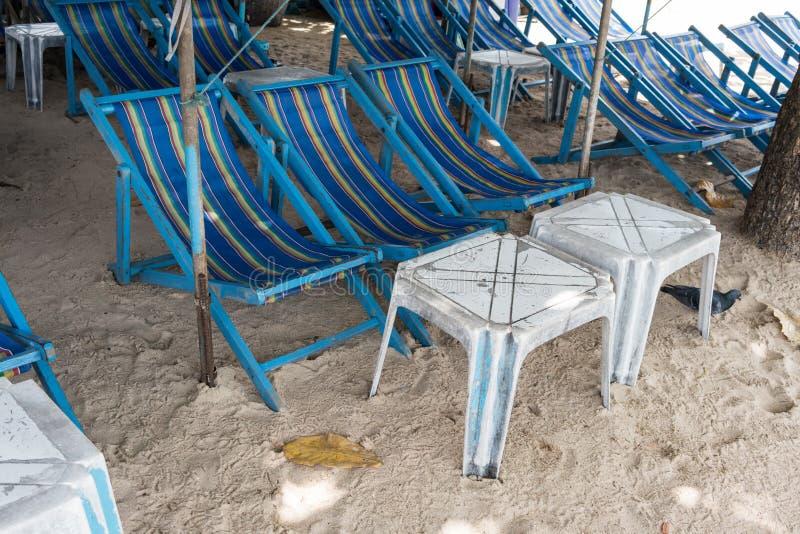 Cadeiras azuis alugado da lona da praia e tabela branca sob u colorido foto de stock royalty free