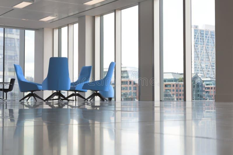 Cadeiras azuis modernas no escritório vazio novo pelas janelas imagens de stock