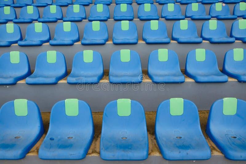 Cadeiras azuis plásticas do estádio do esporte em seguido foto de stock