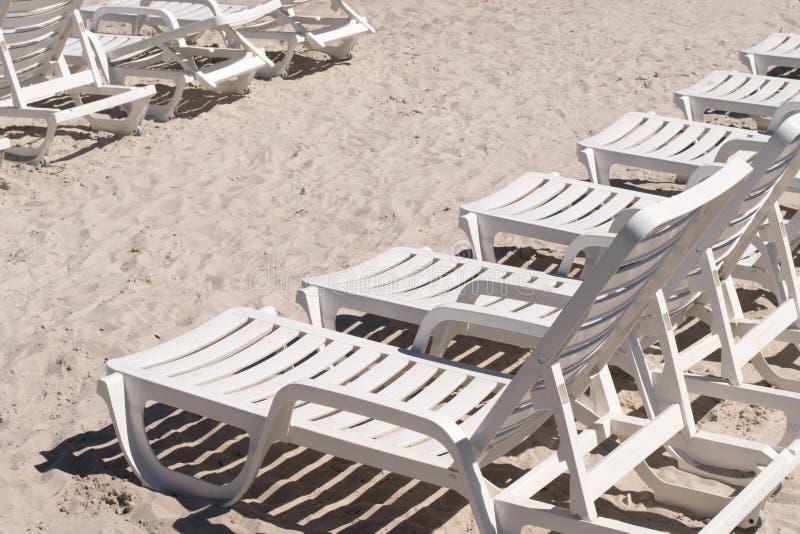 Cadeiras brancas vazias do abrandamento da praia na praia da areia fotografia de stock
