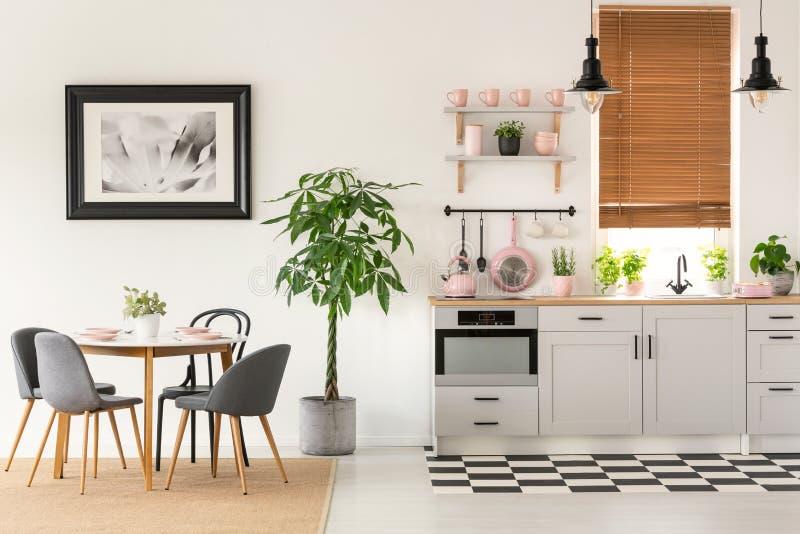 Cadeiras cinzentas na mesa de jantar no interior brilhante com cartaz e p imagens de stock