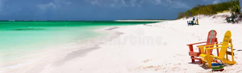 Cadeiras coloridas na praia das caraíbas imagens de stock