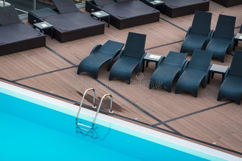 Cadeiras da piscina e de plataforma para o abrandamento imagem de stock royalty free