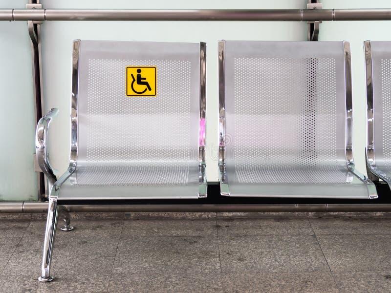 Cadeiras de aço inoxidável no estação de caminhos-de-ferro com o signage deficiente para facilitar o uso de serviços do trem para foto de stock