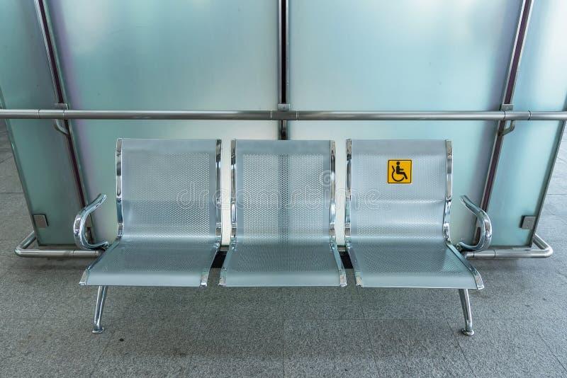 Cadeiras de aço inoxidável no estação de caminhos de ferro com signag deficiente foto de stock