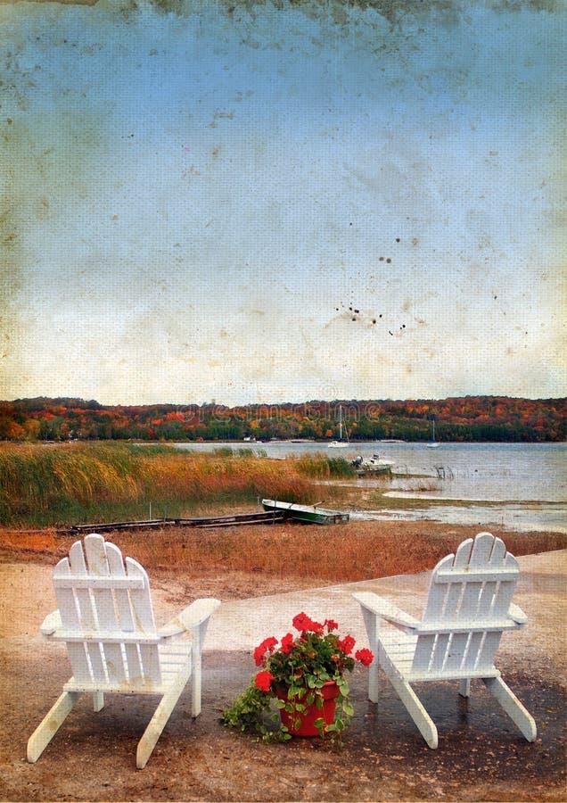 Cadeiras de Adirondack pelo mar no fundo de Grunge imagens de stock