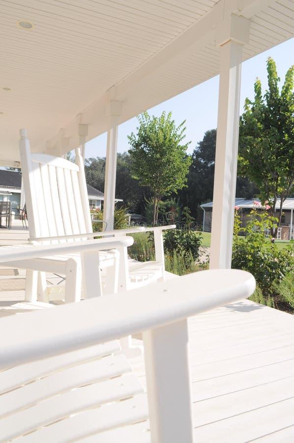 Cadeiras de balanço em um envoltório branco em torno do patamar fotografia de stock