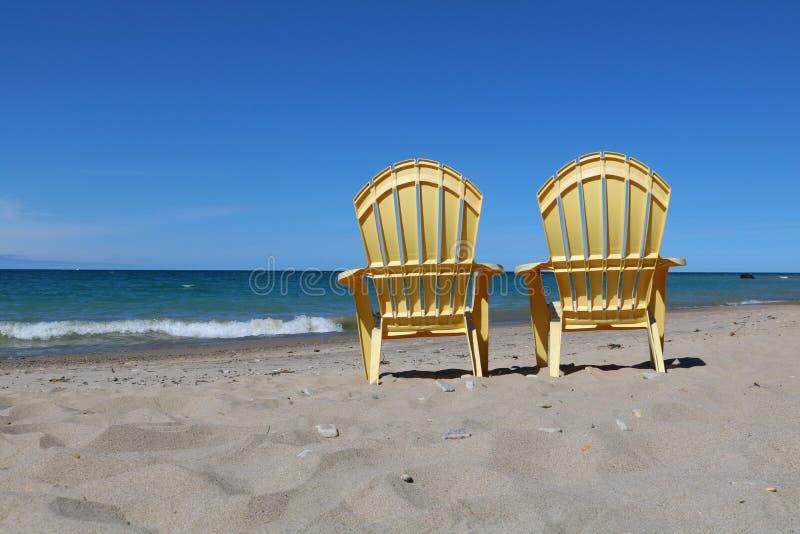 Cadeiras de gramado plásticas amarelas na borda da água em um dia ensolarado bonito da queda imagens de stock