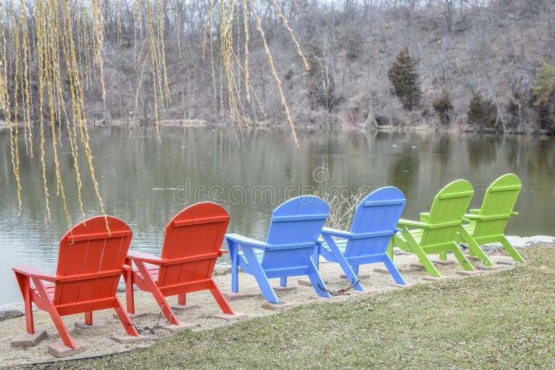 Cadeiras de gramado vermelhas, azuis e verdes pelo lago foto de stock royalty free