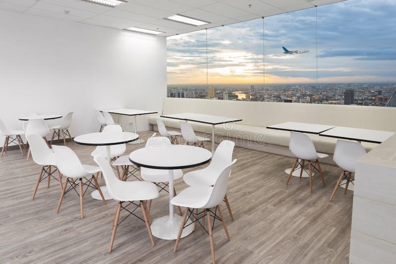 Cadeiras de madeira brancas na sala de jantar do escritório moderno com janelas foto de stock