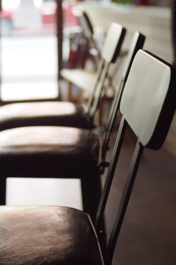 Cadeiras de madeira de Brown arranjadas nas fileiras no escritório imagem de stock