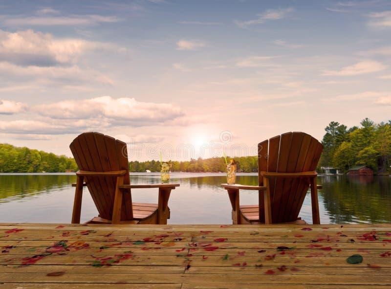 Cadeiras de madeira em uma plataforma do lago imagem de stock