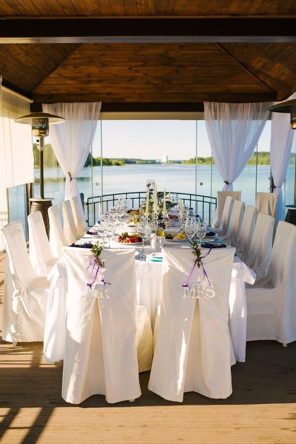 Cadeiras de noiva e noivo em capas brancas com as palavras 'mr' e 'mrs' num casamento ao ar livre Banquet imagem de stock