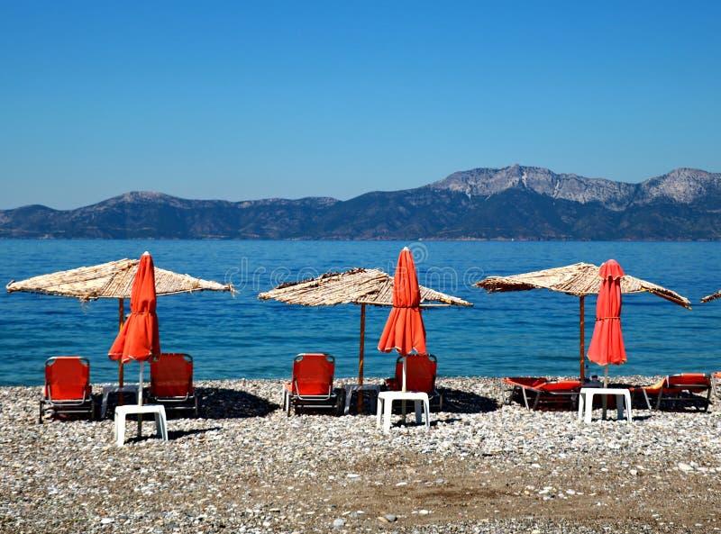 Cadeiras de plataforma alaranjadas sob os parasóis na praia imagem de stock