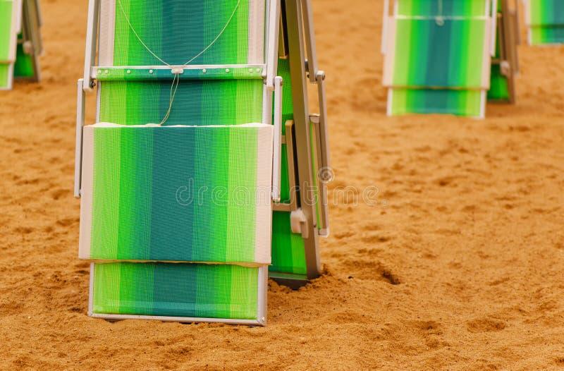 Cadeiras de plataforma dobradas no Sandy Beach no beira-mar fotografia de stock royalty free