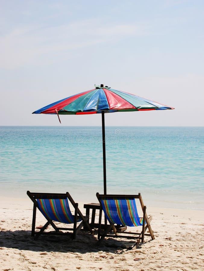 Cadeiras de plataforma em uma praia arenosa branca fotografia de stock