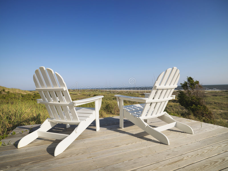 Cadeiras de plataforma na praia. imagem de stock
