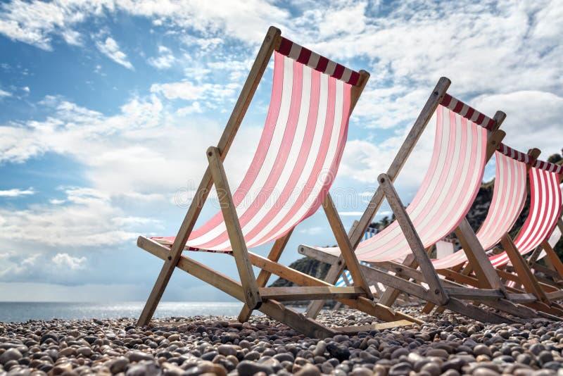 Cadeiras de plataforma na praia nas férias de verão do beira-mar foto de stock royalty free
