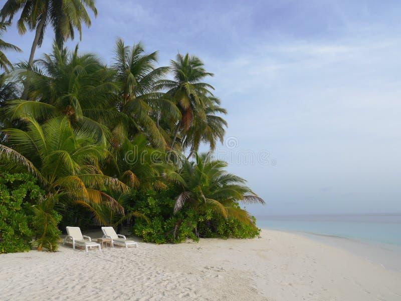 2 cadeiras de praia brancas na praia da areia da ilha tropical foto de stock