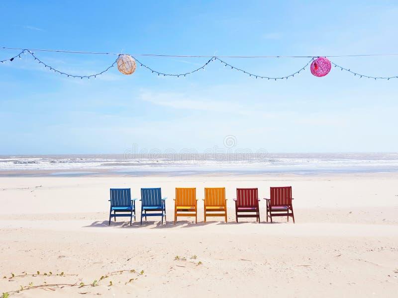 Cadeiras de praia coloridas em uma praia branca larga da areia que enfrenta o oceano em Vietname com lampions e uma corrente clar imagens de stock royalty free