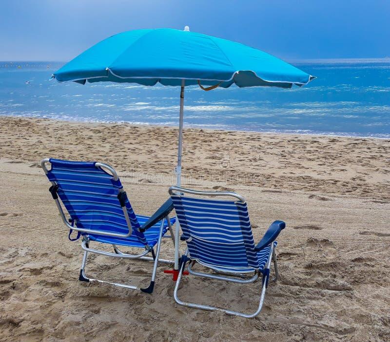 Cadeiras de praia com guarda-chuva azul e a praia bonita em um dia ensolarado Benidorm, Espanha imagens de stock royalty free