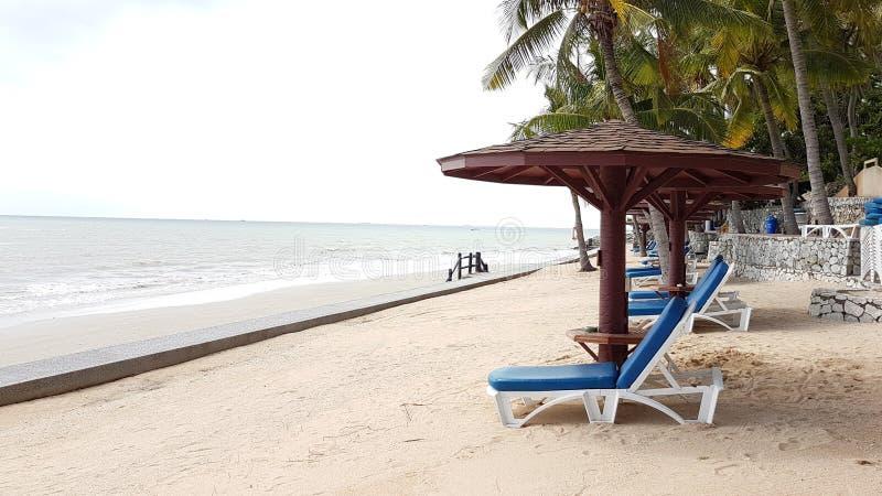 Cadeiras de praia de madeira brancas com coxim azul e máscaras de madeira em t foto de stock royalty free