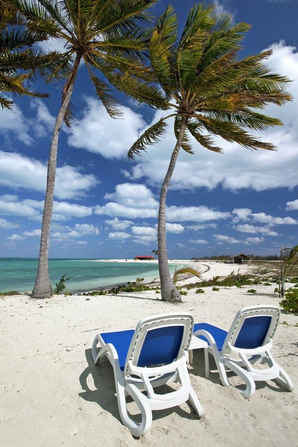 Cadeiras de praia na praia do nascer do sol foto de stock