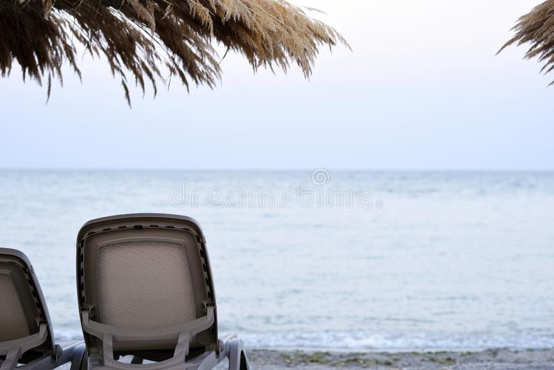 Cadeiras de praia vazias na areia da costa fotos de stock royalty free