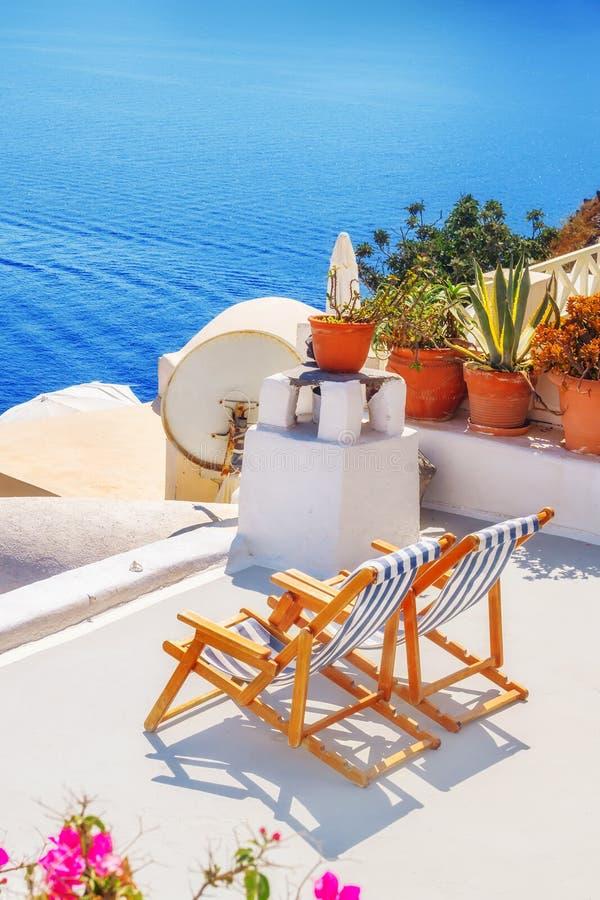 Cadeiras de sala de estar com uma vista do caldera, vila de Oia, Santorini imagens de stock royalty free