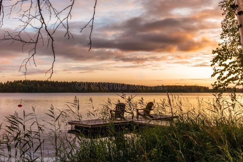 Cadeiras de sala de estar de madeira no por do sol em um cais nas costas do lago calmo Saimaa em Finlandia sob um céu nórdico no  fotos de stock royalty free