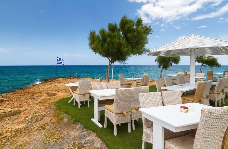 Cadeiras de tabelas e guarda-chuva de madeira no mar de negligência da praia rochosa e na bandeira grega, Creta, Grécia foto de stock