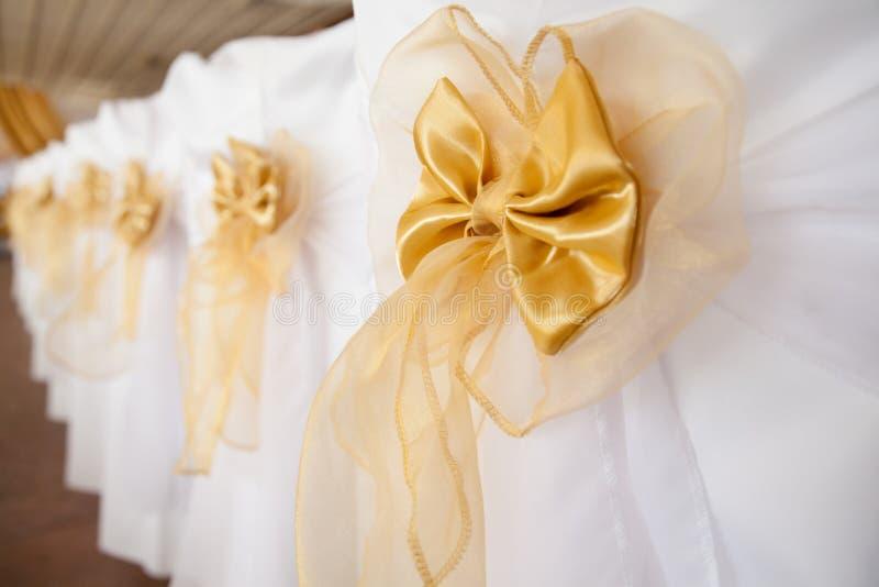 Cadeiras do casamento decoradas com a fita dourada da cor imagem de stock