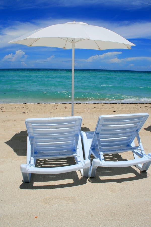 Cadeiras do guarda-chuva e da sala de estar de praia imagem de stock