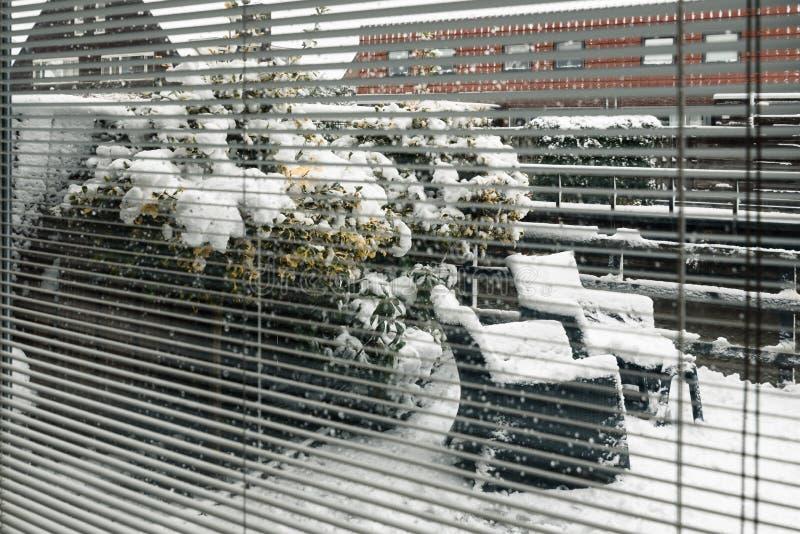 Cadeiras do quintal através das cortinas de janela sob a neve fotos de stock