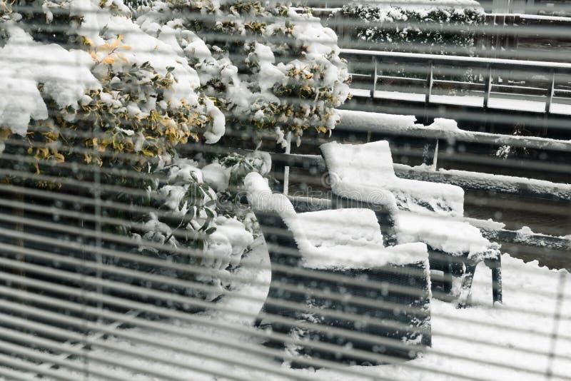 Cadeiras do quintal através das cortinas de janela sob a neve fotos de stock royalty free