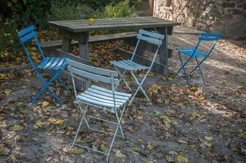 Cadeiras dos azuis no jardim do terraço no outono imagem de stock