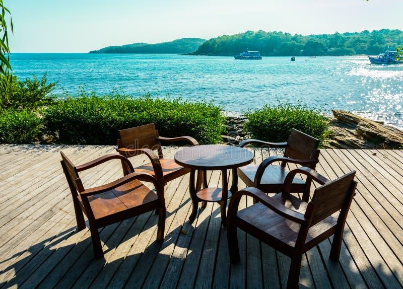 Cadeiras e tabela de madeira no terraço aberto do beira-mar fotografia de stock royalty free