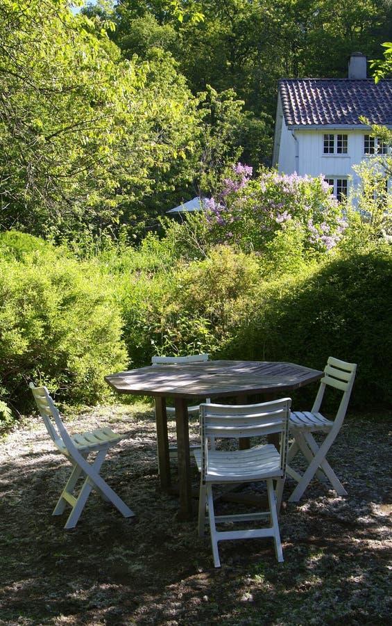 Cadeiras e tabela em um jardim imagem de stock