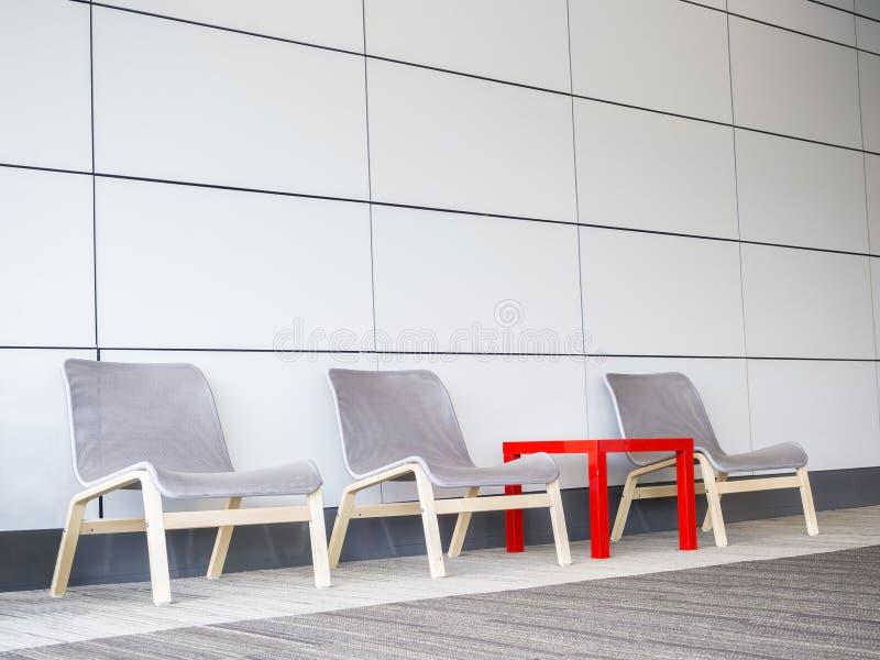 Cadeiras e tabela pequena no assoalho ao lado da parede moderna fotos de stock