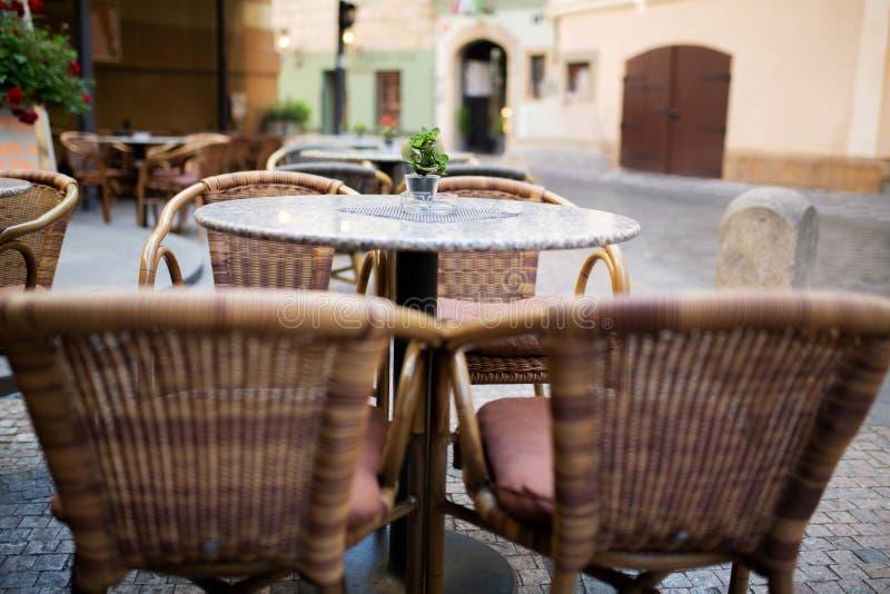 Cadeiras e tabelas vazias do rattan fora de um restaurante da rua na cidade fotografia de stock