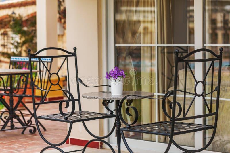 Cadeiras elegantes forjadas na varanda de uma casa de campo dentro fotografia de stock royalty free
