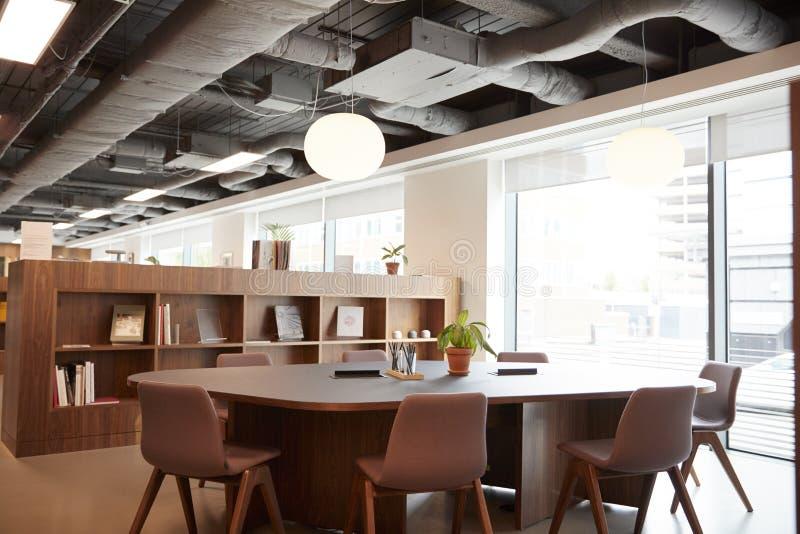 Cadeiras em torno da tabela na área de encontro moderna vazia do escritório fotos de stock