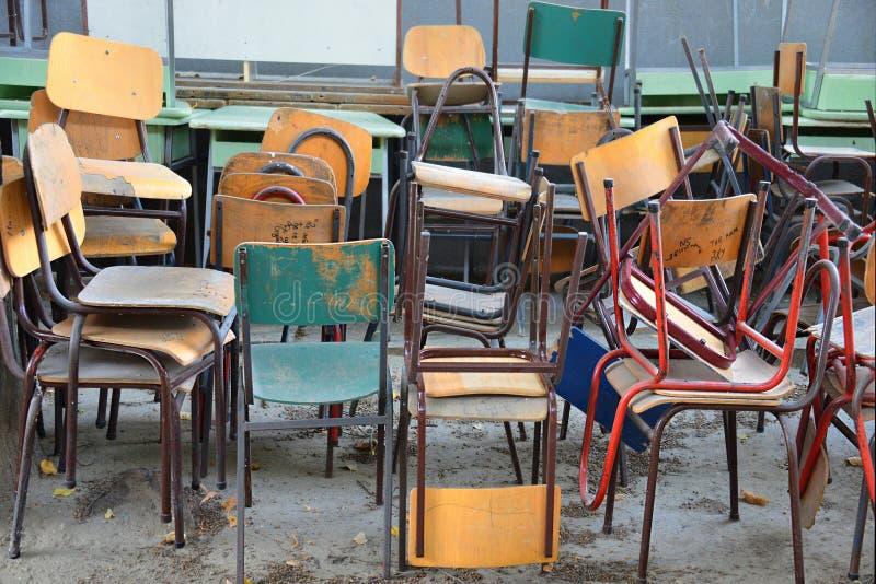 Cadeiras jogadas velhas da escola fotos de stock
