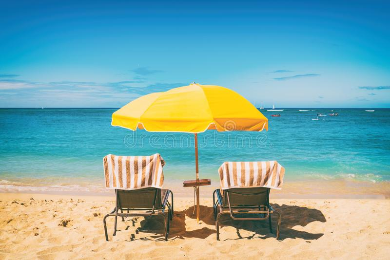 Cadeiras lounging do feriado da praia sob o fundo das férias do guarda-chuva de sol Curso tropical do ver?o fotos de stock