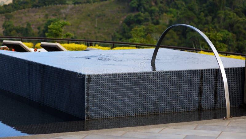 Cadeiras luxuosas do Jacuzzi e de sala de estar da banheira de hidromassagem da associação da infinidade na piscina superior do h imagem de stock