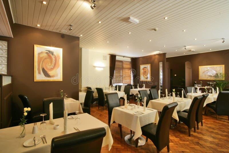 Cadeiras marrons suportadas elevadas em um restaurante fotos de stock