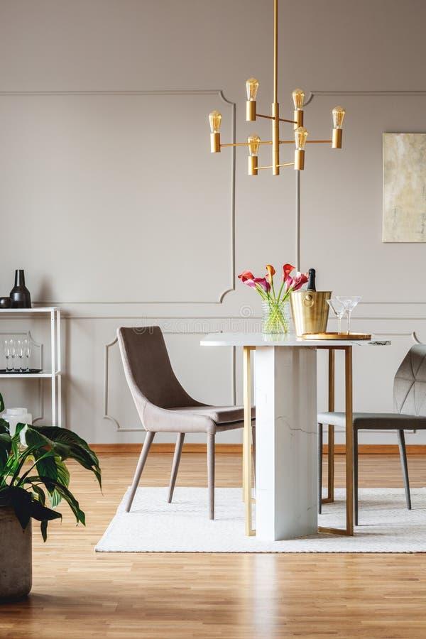 Cadeiras na mesa de jantar com as flores no interior brilhante do apartamento com a lâmpada da planta e do ouro Foto real imagens de stock