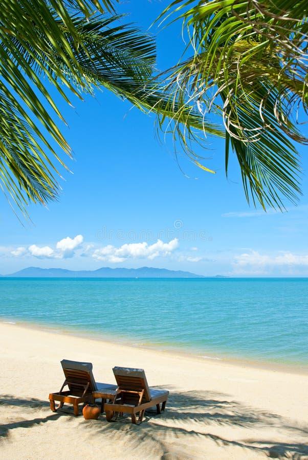 Cadeiras na praia perto do mar imagem de stock