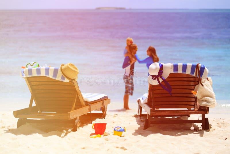 Cadeiras na praia tropical, férias da praia da família fotografia de stock
